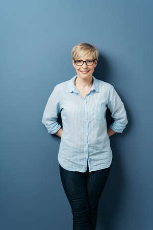Front portrait of smiling middle-aged woman with short blond hair, wearing glasses, blue shirt and dark jeans, standing with her hands behind her back, against plain blue background in studio Banque d'images