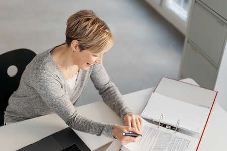 Happy businesswoman reading a report or notes in a large office binder at her desk with a pleased smile in a high angle view