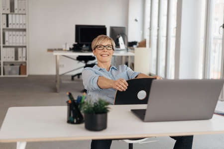Happy thoughtful businesswoman sitting daydreaming or planning her business strategy seated on a reversed chair looking up with a beaming smile in a high key office with copy space