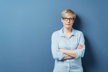 Portrait of mature blonde woman wearing glasses standing against blue background with arms crossed Banque d'images