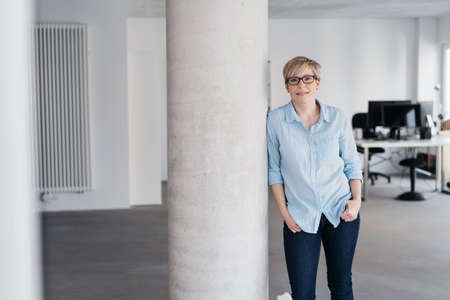 Middle-aged woman in glasses and blue shirt, with short blond hair, standing in spacious office leaning on white column and looking at camera with a smile. Front portrait with copy space Banque d'images