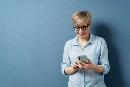 Middle-aged woman with short blond hair, wearing glasses and blue shirt, smiling while texting using mobile phone in her hands. Half-length front portrait against studio blue backgrund with copy space