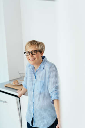 Smiling middle-aged blond woman wearing glasses relaxing in her kitchen leaning on the counter and turning to look at camera Banque d'images
