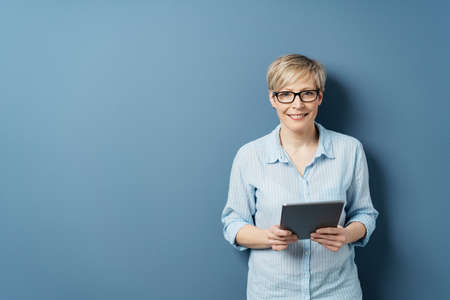Smiling middle-aged woman with short blond hair, wearing glasses and blue shirt, standing with tablet computer in her hands and looking at camera. Front portrait on blue background with copy space