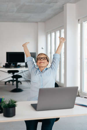 Happy successful businesswoman stretching her arms above her head with a beaming smile of satisfaction at her desk in a high key office with copy space Banque d'images
