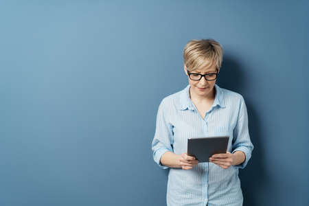 Middle-aged woman with short blond hair in glasses and blue shirt, standing and reading from tablet. Half-length front portrait against plain blue studio background with copy space Banque d'images