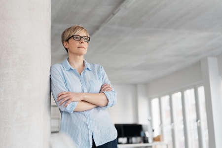 Low-angle portrait of a beautiful young woman with modern blond short haircut leaning on a column indoors while looking away and thinking of future Banque d'images