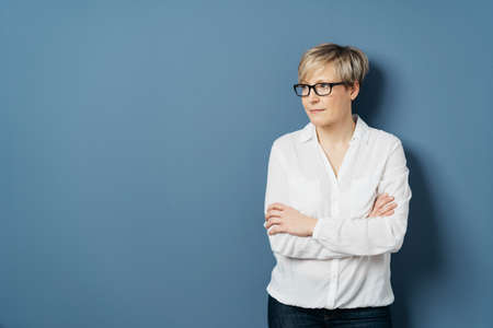 Middle-aged woman with short blond hair, wearing white blouse, standing with crossed hands and looking aside at copy space on plain blue studio background Banque d'images