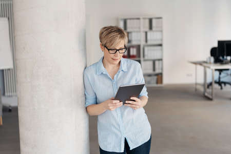 Relaxed woman standing reading on a tablet pc in a bright spacious open plan office with an engrossed expression, with copy space