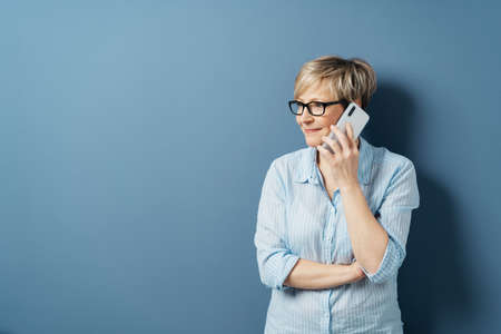 Middle-aged woman with short blond hair, in glasses and blue shirt, standing and looking aside while talking by the phone. Half-length front portrait against blue background in studio with copy space Banque d'images