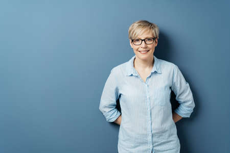 Smiling middle-aged woman with short blond hair, in glasses and blue shirt, standing with her hands behind her back. Half-length front portrait against plain blue background in studio with copy space