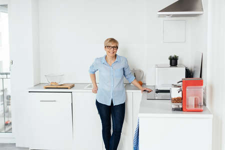 Happy friendly smiling housewife in her kitchen standing leaning on the counter looking at camera with copy space