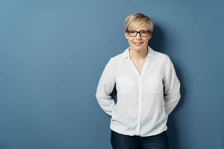 Attractive blond woman wearing glasses over a blue studio background with copy space standing looking thoughtfully at the camera