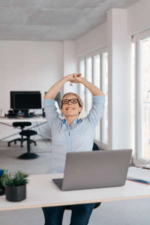 Happy businesswoman stretching her arms above her head with a beaming smile seated at a laptop in a high key office with copy space Banque d'images