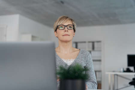 Thoughtful troubled businesswoman wearing glasses seated at her desk behind a laptop computer in a low angle view past a potted plant
