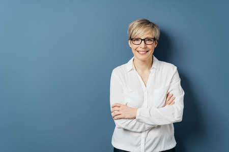 Beautiful smiling middle-aged woman with short blond hair, wearing glasses and white blouse, standing against plain blue studio background with copy space with her arms crossed and looking at camera