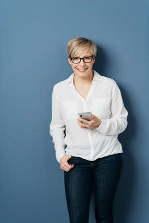 Front portrait of a woman with short blond hair, in glasses, white blouse and black jeans, standing with a phone in her hand against blue background in studio and smiling at camera