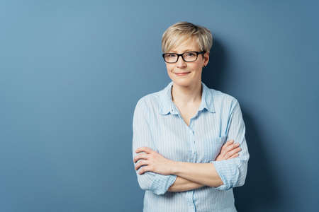 Middle-aged woman with short blond hair, in blue shirt and wearing glasses, standing with her arms crossed and looking at camera with modest smile. Half-length front portrait on blue with copy space Banque d'images