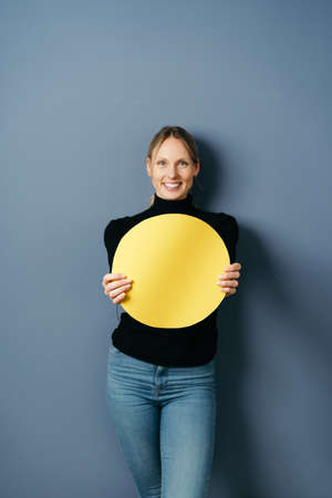 Smiling happy young woman holding up a blank colorful yellow paper circle in front of her chest against a blue studio background in a three quarter portrait