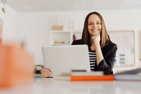 Smiling confident businesswoman with chin on hand looking at camera as she sits working at a laptop in the office in a low angle view Banque d'images