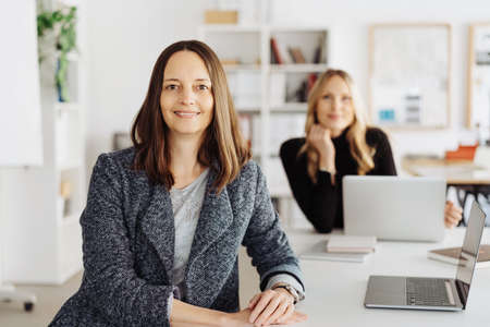 Smiling confident attentive smart middle-aged businesswoman turning to look at the camera watched by a female colleague working at a laptop in the background in a modern office