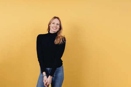 Cute vivacious young woman with long blond hair wearing jeans and a black turtle neck posing over a colorful yellow studio background with copyspace