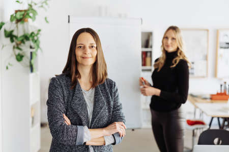 Confident smart professional businesswoman with a warm friendly smile standing with folded arms in the office looking at camera watched by a smiling female colleague or partner in the background in a leadership concept