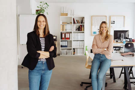 Two happy relaxed successful smiling businesswoman posing in aa bright spacious office standing with folded arms looking at the camera with selective focus to a woman in her twenties Banque d'images