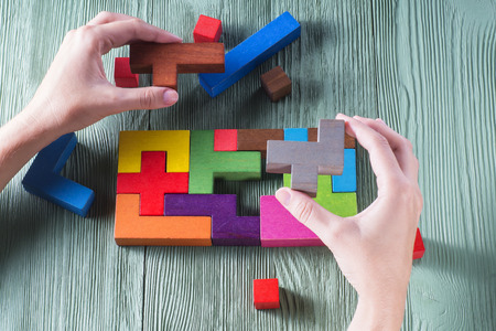 logical: Hand holding wooden puzzle element. Hand sets the last element of the puzzle. The concept of logical thinking. Geometric shapes on a wooden background. Tetris toy wooden blocks.