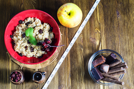 Healthy vs  unhealthy food. Concept of making choice of food: fruit, oatmeal  or candy, separated by a measuring tape. Time for slimming.