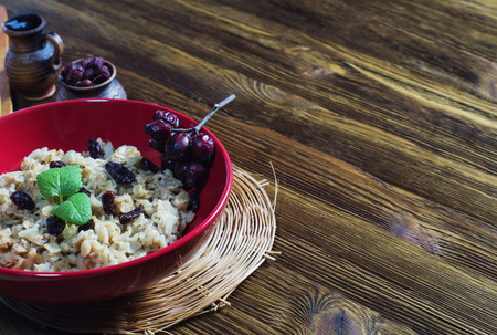 Oatmeal with raisins, branch of wild rose and mint in a red ceramic plate on a wooden table.