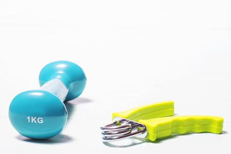 Dumbbell and hand expander on a white background.