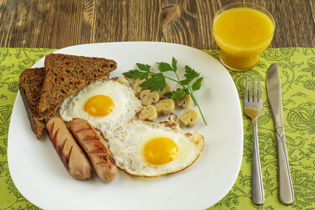 Fried eggs with sausage, marinade mushrooms and rye bread served on a plate on napkin.