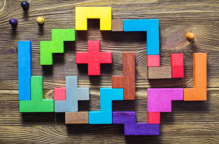 Der Mann im Labyrinth, flach lag. Das Konzept einer Geschäftsstrategie, Analyse, nach Lösungen zu suchen, die Suche ausgegeben. Labyrinth von bunten Holzklötzen, tetris, Draufsicht.
