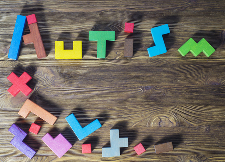 asperger: Word Autism built of wooden puzzles on a wooden background.