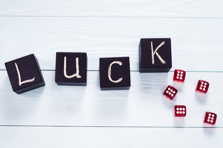 black luck: Luck word written in black wooden cubes and red dice on a blue wooden background, flat lay. Concept for business risk, chance, good luck or gambling, top view.