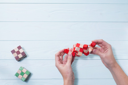 conundrum: Logic background. The concept of logical thinking. Wooden colorful cubes, puzzle. Hands holding wooden conundrum.