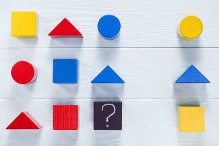 iq: IQ test. Choose correct answer. Logical tasks composed of geometric wooden shapes.  Childrens educational logical task, flat lay. Stock Photo