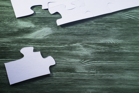 logical: The concept of logical thinking. Logical conundrum. White jigsaw puzzle on a wooden background. Placing missing a piece of puzzle.
