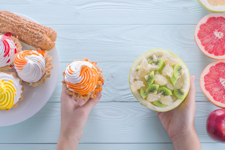 Hands of a young woman holding a cake and fruit salad, making a choice between them. Woman making a choice between sweets and fruits. Healthy vs unhealthy food. top view, flat lay.
