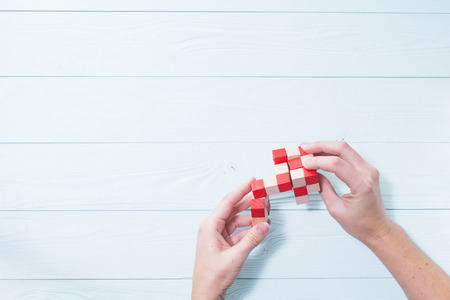 logical: Logic background. The concept of logical thinking. Wooden colorful cubes, puzzle. Hands holding wooden conundrum.