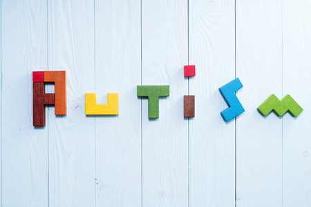 developmental disorder: Word Autism built of colorful wooden blocks on a blue wooden background with copy space, top view. Concept of autism word, flat lay. Autism Spectrum Disorder (ASD). Stock Photo