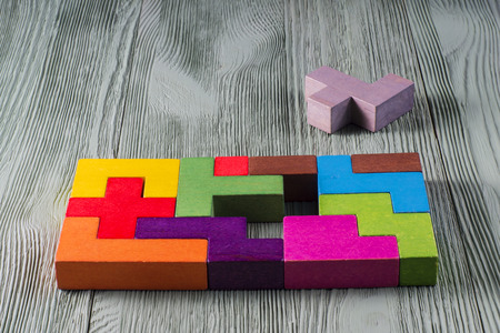logical: The concept of logical thinking. Wooden geometric shapes. Tetris toy wooden blocks on a wooden background.
