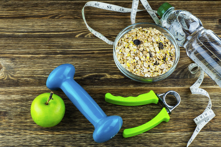 The concept of a healthy lifestyle. Apple, dumbbell, water, expander hand and measuring tape on rustic wooden table.