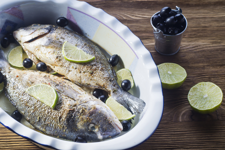 roasting pan: Fresh uncooked dorado with lemon, lime, olives, oil and spices on rustic wooden board. Raw fresh fish with seasonings in roasting pan before baking on brown wooden background.