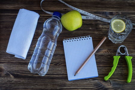 The concept of a healthy lifestyle. Workout and fitness dieting copy space diary. Apple, water, expander hand, and measuring tape on a wooden table.
