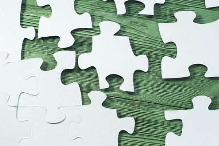 logical: The concept of logical thinking. White jigsaw puzzle on a wooden background, flat lay. Business concept with white jigsaw puzzle on green wooden background. Placing missing a piece of puzzle.