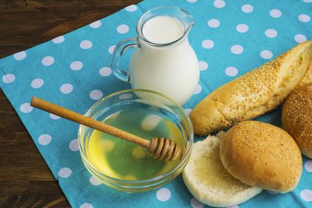 Bread, milk, honey on the tablecloth.