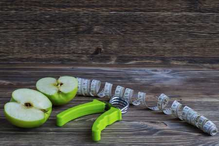 The concept of a healthy lifestyle. Green apples, measuring tape and hand espander.
