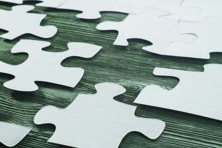 logical: The concept of logical thinking. Logical conundrum. White jigsaw puzzle on a wooden background. Business concept with white jigsaw puzzle on green wooden background. Placing missing a piece of puzzle.